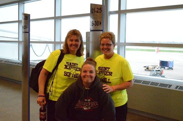 The SXU softball coaching staff gets together for a photo before boarding.