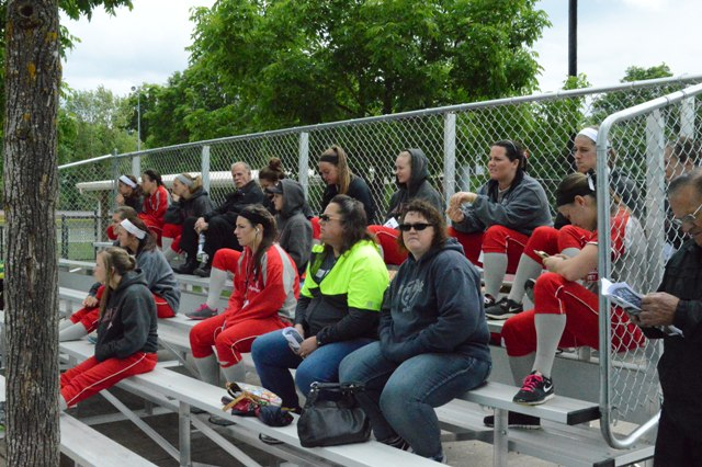 The SXU softball team watches the early game between Concordia and Corban.