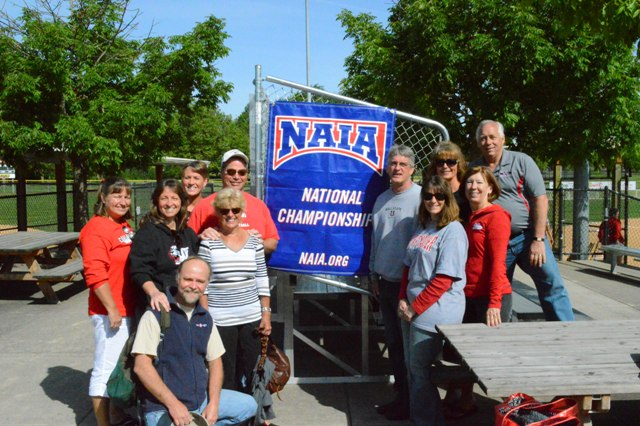 Some of the parents pose by the NAIA National Championship banner