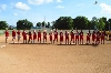 SXU softball players line up for the National Anthem