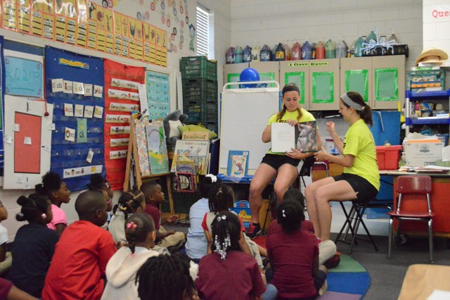 Freshmen Nicole Nonnemacher and Denise Anderson reading to a group of Kindergartner's.