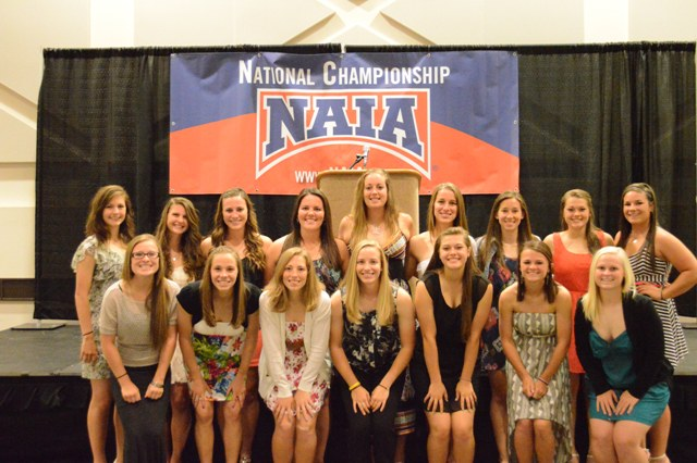 The team posing in front of the podium in the banquet hall.