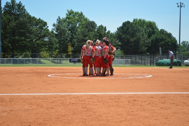 The team has a meeting at the pitcher's circle before the start of the game.