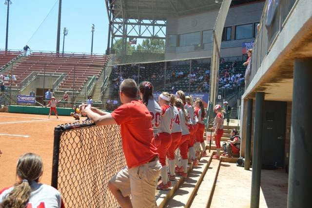 The player's line the dugout fence cheering on freshman Kasey Kanaga.