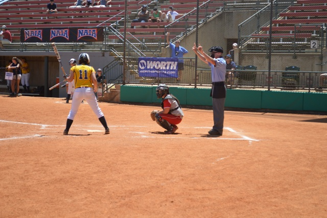 Sophomore catcher Megan James look's to the dugout for what pitch to call.