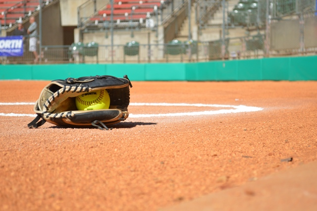 An artistic shot of a glove and softball.