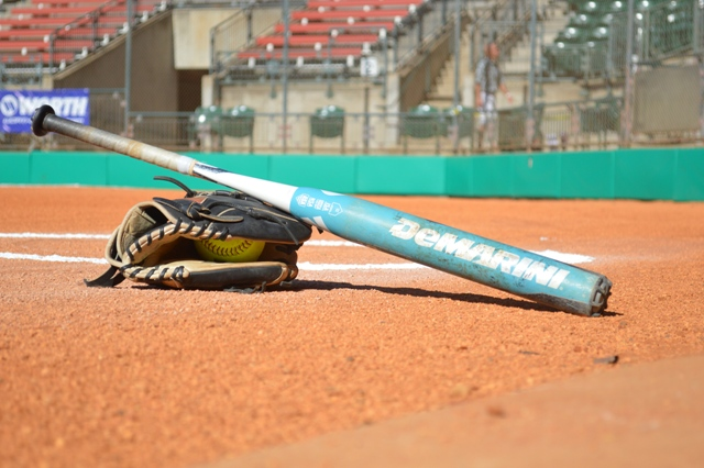 An artistic shot of a glove, a softball and a bat.