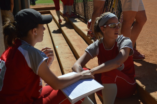 Freshman Denise Anderson and sophomore Alex Bahner watch the game from the dugout.