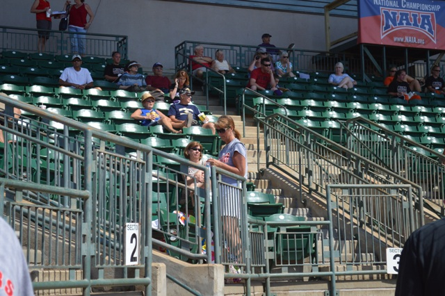 Some of the parents sit near home plate during the game.