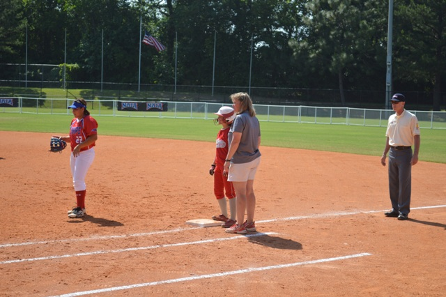 Junior Katie Houlihan, talking with coach Kim Kosinski, stands on first after a base-hit.