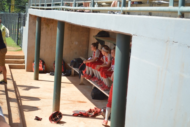 Some of the ladies stay in the shade of the dugout during a warm day.