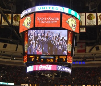 SXU football players cheer when their seating section was displayed on the United Center Jumbotron