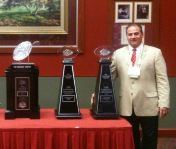 SXU football coach Mike Feminis posing with the 2011 AFCA Coach of the Year trophies