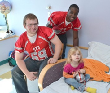 Junior Tim Beyer (left) and senior Carven Proctor (right) visit a patient at Hope Advocate Children's Hospital