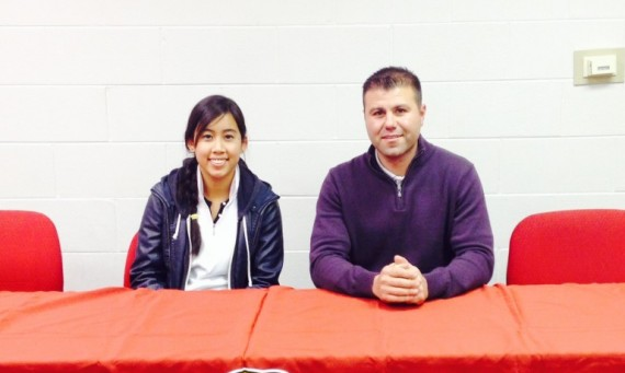 Hannah Cruz joins SXU golf coach Mike Mandakas at a recent signing for the SXU women's golf team