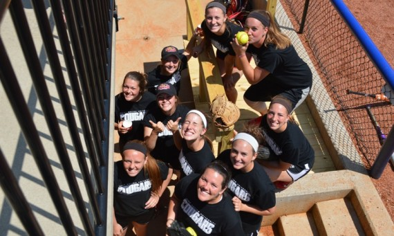 A group of the SXU softball players pose for a photo in the dugout at Lindsey Wilson Sports Park