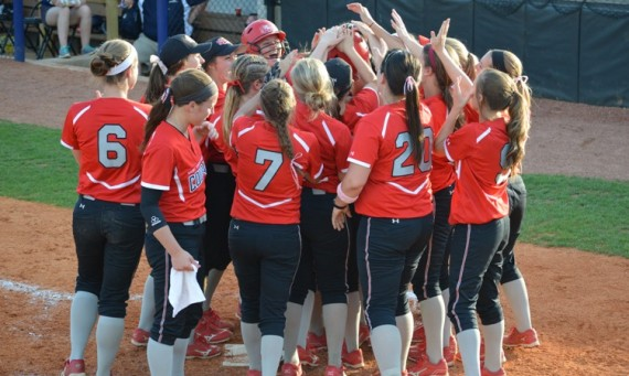 The SXU softball team greets junior Amanda Hainlen at home plate to celebrate after her sixth-inning homer