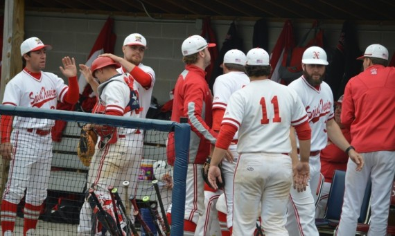 The SXU baseball team celebrates in the dugout Tuesday after a big inning against St. Francis (Ill.)